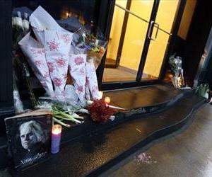 A passer-by stops at a makeshift memorial outside the home of actor Philip Seymour Hoffman, Feb. 3, 2014, in New York.