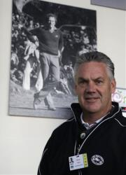 Steve John, CEO of the Monterey Peninsula Foundation and tournament director of the AT&T Pebble Beach Pro-Am golf tournament, poses beneath a photograph of Clint Eastwood Friday.