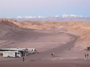 Tour buses wait for visitors to return from watching the sunset over the desolate Valle de la Luna in Chile's Atacama Desert.