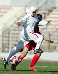 Iran's Jahanchi Masoomeh, in white, fights for the ball with Syria's Manar Monther during a soccer match at Amman Stadium, Jordan,  Monday Sept. 3, 2007.
