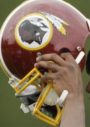 n this May 1, 2009 file photo, the Washington Redskins' Marko Mitchell puts his helmet on during an NFL football minicamp in Ashburn, Va.
