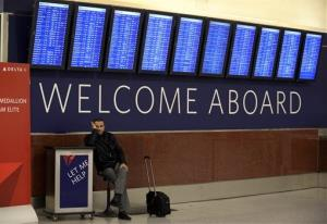 A passenger waits under the departure board showing hundreds of cancellations at Hartsfield-Jackson International Airport on Tuesday, Feb. 11, 2014 in Atlanta.