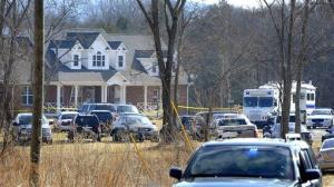 Law Enforcement cars fill the front yard of a rural home in Lebanon, Tenn. where a package sent there exploded Monday, killing 74-year-old lawyer Jon Setzer.