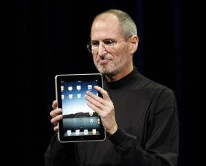 In this Jan. 27, 2010 file photo, Apple CEO Steve Jobs shows off the new iPad during an event in San Francisco.