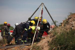 Emergency rescue workers attempt to free trapped illegal miners at a disused gold mine shaft near, Benoni, South Africa, Sunday, Feb. 16, 2014.