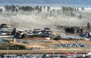 Waves of tsunami hit residences after a powerful earthquake in Natori, Miyagi prefecture (state), Japan, Friday, March 11, 2011.