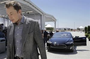 In this June 2012 file photo, Tesla CEO Elon Musk walks past the Tesla Model S after a news conference at the Tesla factory in Fremont, Calif.