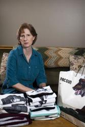 Judy Cox sits for a portrait next to a stack of T-shirts with what she believes are pornographic designs.