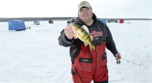 Steve Dahl, owner of the Perch Patrol, shows off the first perch he caught on Saturday, Feb. 8, 2014 on Devils Lake, ND.