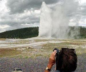 In this Friday, Aug. 15, 1997 file photo, an unidentified visitor to the Yellowstone National Park photograph the Old Faithful geyser as it rockets 100-feet skyward in Wyoming.