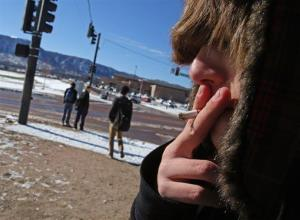 A high school student, who preferred not to be identified, smokes a cigarette in Monument, Colo., Thursday Feb. 20, 2014.