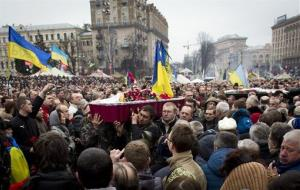 Coffins with bodies of protesters killed in recent clashes are carried through the crowd in central Kiev.