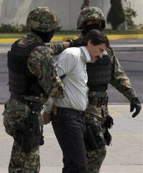 Joaquin El Chapo Guzman is escorted to a helicopter in handcuffs by Mexican navy marines at a navy hanger in Mexico City, Mexico, Saturday, Feb. 22, 2014.