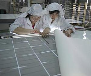 In this July 17, 2013 photo, workers assemble solar panels at a factory in Hefei, in central China's Anhui province.