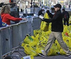 A worker returns a bag containing a runner's personal effects near the finish line of the Boston Marathon following the bombing, in this April 16, 2013 file photo.