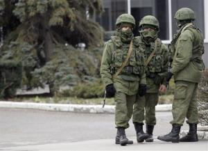 Unidentified armed men patrol in front of the airport in Simferopol, Ukraine, Friday.