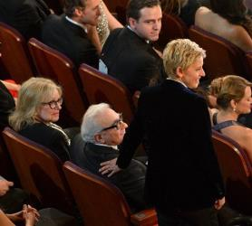 Ellen DeGeneres stands in the audience next to Martin Scorsese during the Oscars at the Dolby Theatre on Sunday, March 2, 2014, in Los Angeles.