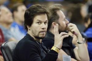 Actor Mark Wahlberg sits courtside during the NCAA college basketball game between Southern California and UCLA, Sunday, Jan. 5, 2014, in Los Angeles.