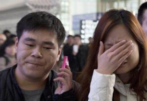 A woman cries at the arrival hall of the International Airport in Beijing Saturday.