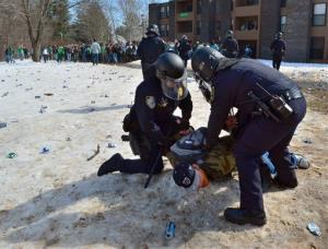 Police detain a participant in the pre-St. Patrick's Day Blarney Blowout near the University of Massachusetts in Amherst, Mass. on Saturday, March 8, 2014.