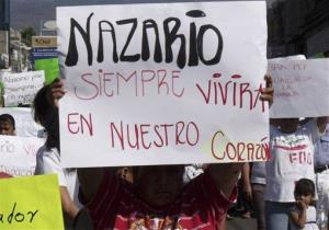 In this Dec. 12, 2010 file photo, a man holds a sign that reads in Spanish Nazario will always live in our hearts, referring to La Familia drug cartel leader Nazario Moreno Gonzalez.