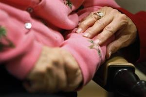 The director of an Alzheimer's assisted-living facility in Washington puts her hand on the arm of a resident.
