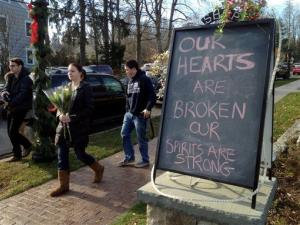 Jessica Henderson, 19, walks past a sign with a bouquet of flowers to lay at a memorial at The Sandy Hook School in Newtown, Conn., on Saturday, Dec. 15, 2012.