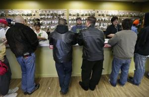 Employees help customers at the sales counter inside Medicine Man marijuana retail store, which opened as a legal recreational retail outlet in Denver on Wednesday Jan. 1, 2014.