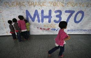 Children read messages and well wishes displayed for all involved with the missing Malaysia Airlines jetliner MH370 on the walls of the Kuala Lumpur International Airport.
