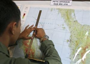 An Indonesian Air Force officer draws a flight pattern flown earlier in a search operation.