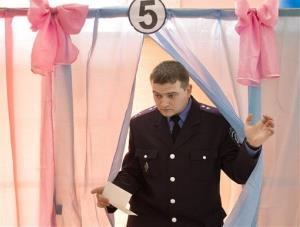 An Ukrainian policeman exits a voting booth after casting his vote in Perevalne, Ukraine, Sunday, March 16, 2014.