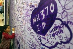 A girl writes a message for passengers aboard a missing Malaysia Airlines plane, at a shopping mall in Petaling Jaya, near Kuala Lumpur, Malaysia, Sunday, March 16, 2014.