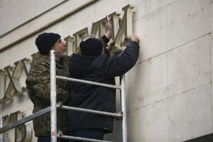 Workers remove old letters from the Crimea Parliament's building in Simferopol, Crimea.