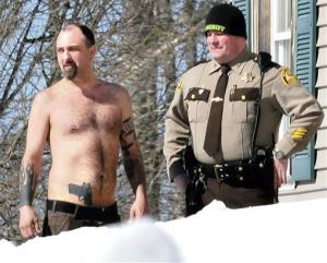 Michael Smith, left, stands beside a Somerset County Sheriff deputy outside his home in Norridgewock, Maine.