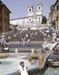 In this 2012 file photo, a tourist cools off in the 17th-century Bernini fountain in front of the historic staircase in Rome.