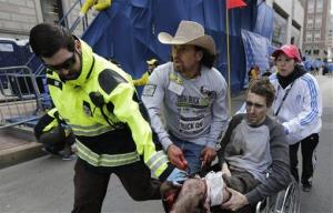 In this April 15, 2013 file photo, an emergency responder and volunteers push Jeff Bauman in a wheel chair after he was injured in an explosion near the finish line of the Boston Marathon.