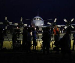 International press gather around a Royal Australian Air Force AP-3C Orion after its return from a search for the missing Malaysia Airlines flight MH370 over the Indian Ocean,  March 24, 2014.