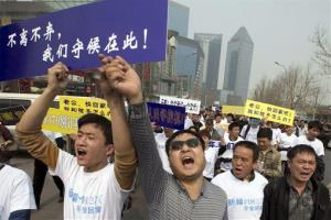 Chinese relatives of passengers shout in protest as they march towards the Malaysian embassy in Beijing today.