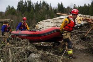 Rescue workers carry an inflatable boat to the flooded area in the debris field caused by the massive mudslide above the North Fork of the Stillaguamish River.