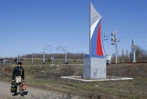 A man walks past a sign marking the border painted in colors of a Russian flag and reading Have a good trip in the village of Vyselki, eastern Ukraine.