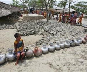 A village girl sits on a vessel as she waits with others in a queue for water supplied in tankers at an area affected by 2009's cyclone Aila in Nildumur, Bangladesh, May 14, 2010.