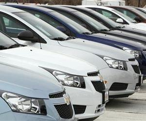 In this Feb. 19, 2012 file photo, a line of 2012 Chevrolet Cruze sedans sit at a dealership in the south Denver suburb of Englewood, Colo.