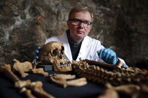 In this Wednesday, March 26, 2014 photo, osteologist Don Walker poses for photographers, with one of the skeletons found by construction workers under central London's Charterhouse Square.