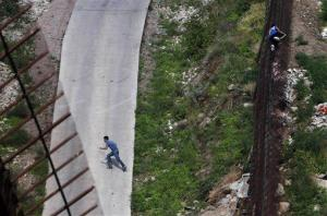 In this July 28, 2011 file photo, two people illegally cross the border fence separating Nogales, Ariz., and Nogales, Sonora, Mexico.