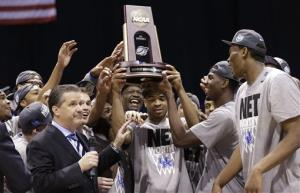 Kentucky's Aaron Harrison and his teammates hold up their trophy after an NCAA Midwest Regional final college basketball tournament game against Michigan Sunday, March 30, 2014, in Indianapolis. Kentucky won 75-72 to advance to the Final Four.
