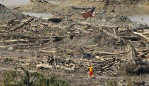 A searcher walks through a channel of water as a flag flies in the debris field Monday, March 31, 2014, at the site of the massive mudslide that hit the community of Oso, Wash. on March 22, 2014.