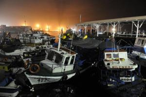 Fishing boats washed ashore by a small tsunami sit in Caleta Riquelme, Chile.