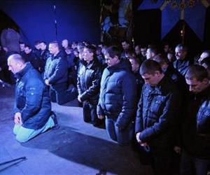 In this photo taken on Monday, Feb. 24, 2014, members of Berkut riot police kneel in front of the crowd as they apologize for their actions in a stage in central Lviv.