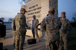 Military personnel wait for a news conference to begin at Fort Hood, Texas, on Wednesday, April 2, 2014.