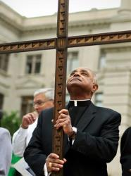 In this April 6, 2012, file photo, Rev. Wilton Gregory, the Archbishop of Atlanta, holds a cross during the 32nd annual Good Friday Pilgrimage at Hurt Park in Atlanta.